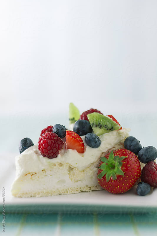 Pavlova slice with summer berries vertical by Kirsty Begg for Stocksy United