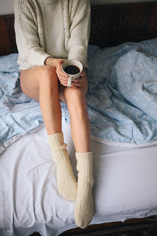 Woman holding cup of coffee sitting on the bed by VeaVea for Stocksy United