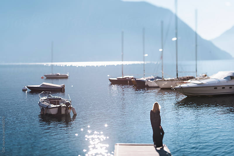 Young woman on the jetty in the lake by Simone Becchetti for Stocksy United
