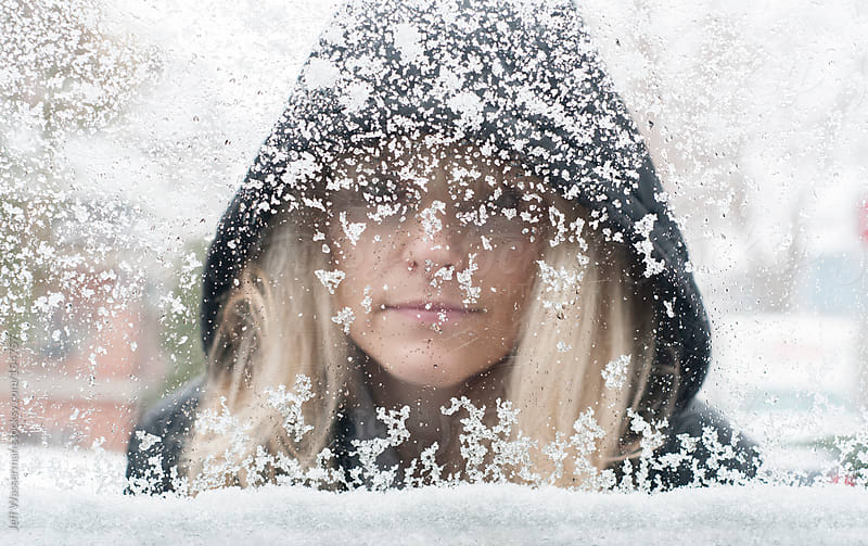 Woman Looks Through Snowy Window by Studio Six for Stocksy United