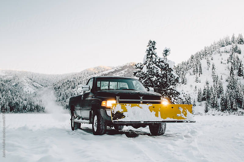 A truck and snow plow on a cold clear morning by Justin Mullet for Stocksy United