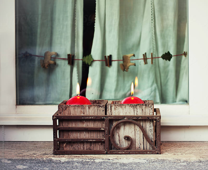 Christmas ornaments: red candles, wooden pot and reindeers garland by Laura Stolfi for Stocksy United