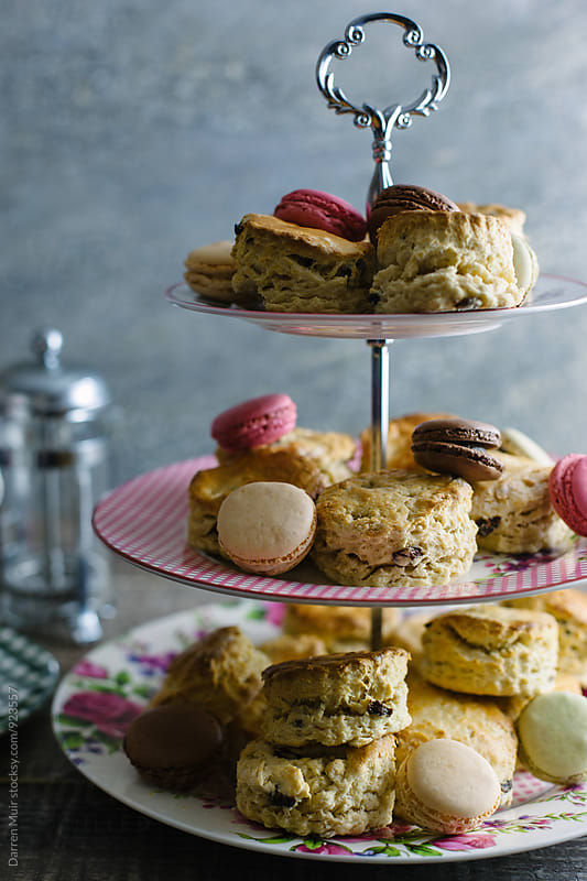 Closeup of a cake stand with scones and macarons. by Darren Muir for Stocksy United