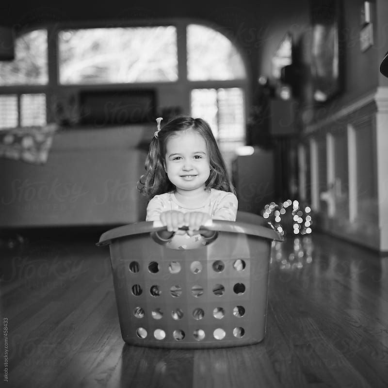 Toddler using a laundry basket for a sled by Jakob for Stocksy United