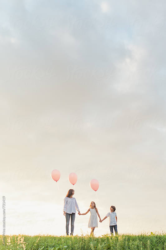 Mother and her kids holding pink balloons against a big cloudy sky by Cindy Prins for Stocksy United