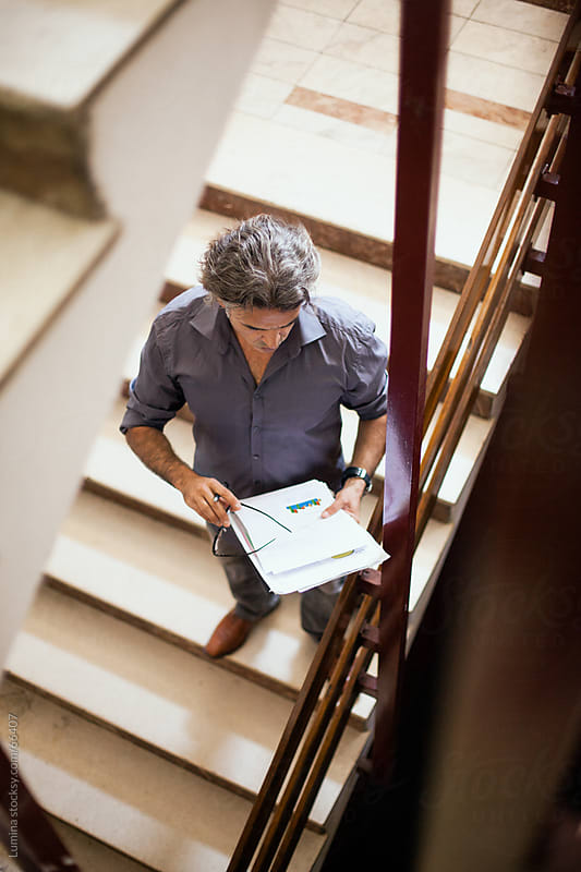 Businessman Reading Documents on the Stairs by Lumina for Stocksy United