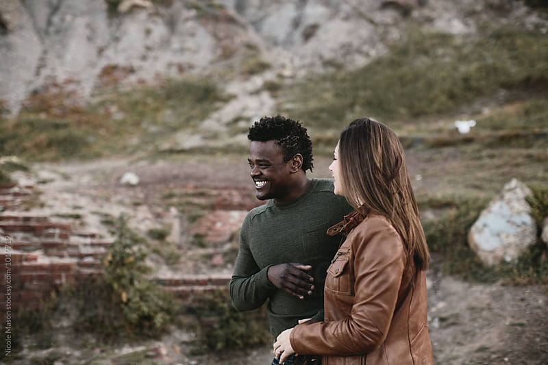 young diverse couple laughing together by Nicole Mason for Stocksy United