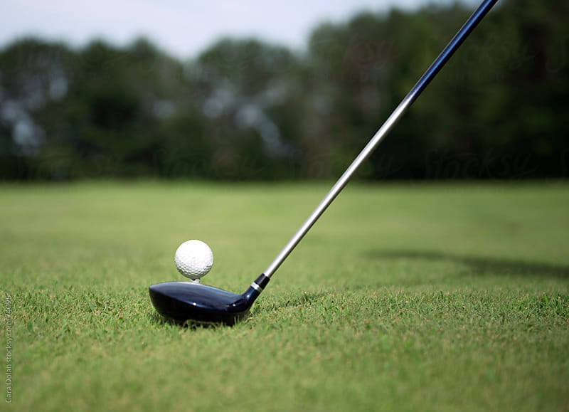 Golfer sets club in front of golf ball on tee by Cara Dolan for Stocksy United