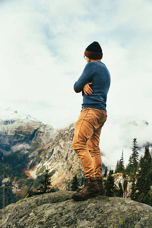 Young Man In Tan Jeans With Arms Crossed Standing On Top Of Rock Looking At Mountains by Luke Mattson for Stocksy United