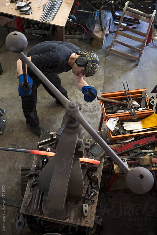 Man working steel in a workshop by Lior + Lone for Stocksy United