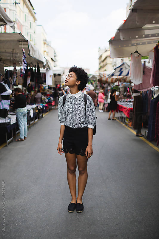 Woman standing among the market stalls by michela ravasio for Stocksy United