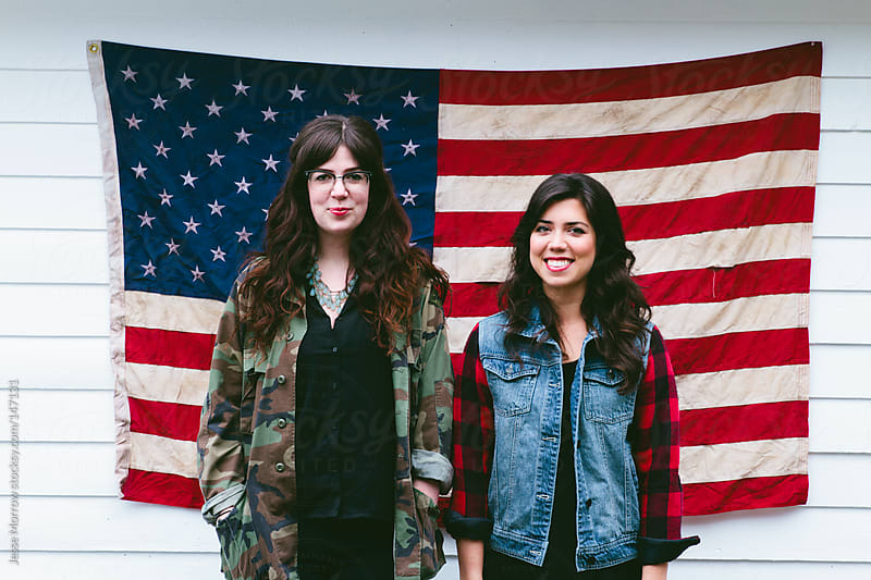 Two girls in front of American flag by Jesse Morrow for Stocksy United