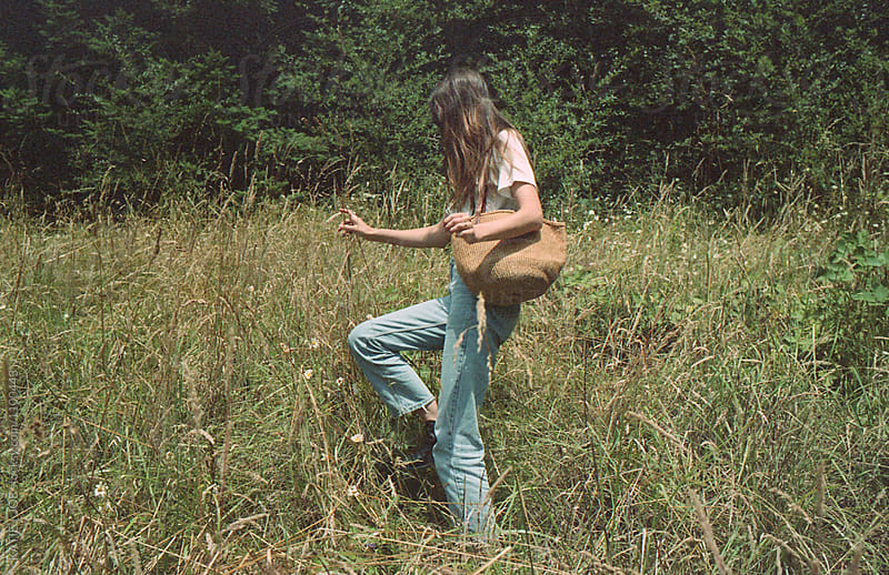 young woman frolicking in a field in jeans with a bag by KATIE + JOE for Stocksy United