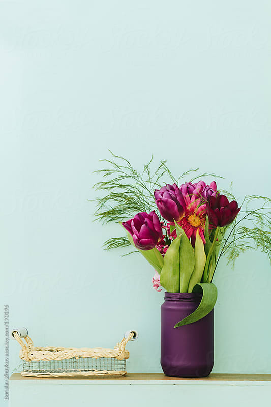 Beautiful purple vase with flowers and handmade tray on bluish wall  by Borislav Zhuykov for Stocksy United
