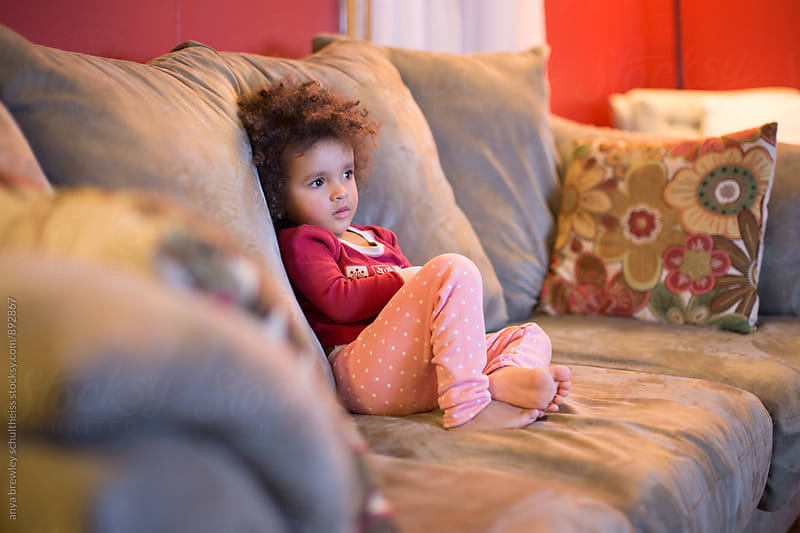 Portrait of young girl with curly hair sitting contently on a couch while watching television by anya brewley schultheiss for Stocksy United