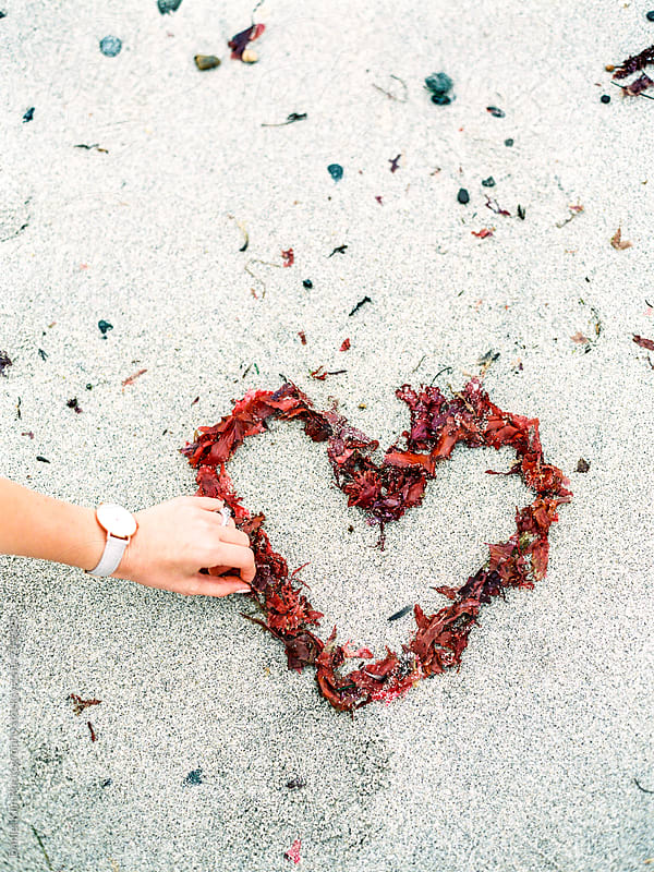 Hand arranging seaweed into heart  by Daniel Kim Photography for Stocksy United
