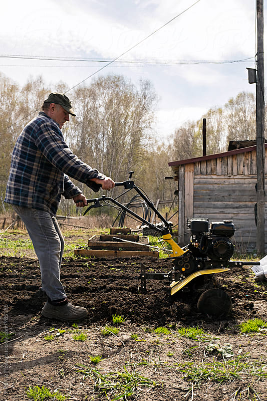 Side view of man working in garden with machine by Danil Nevsky for Stocksy United