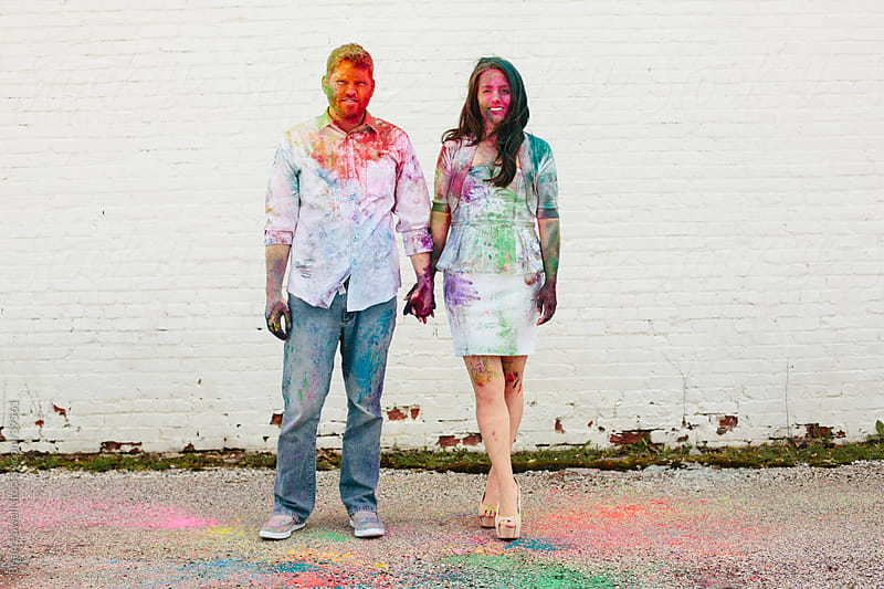couple covered in colorful Holi powder by Brian Powell for Stocksy United