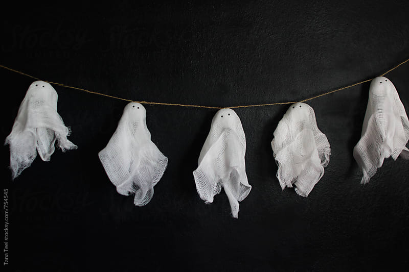 diy craft garland of cheesecloth ghosts on string by Tana Teel for Stocksy United