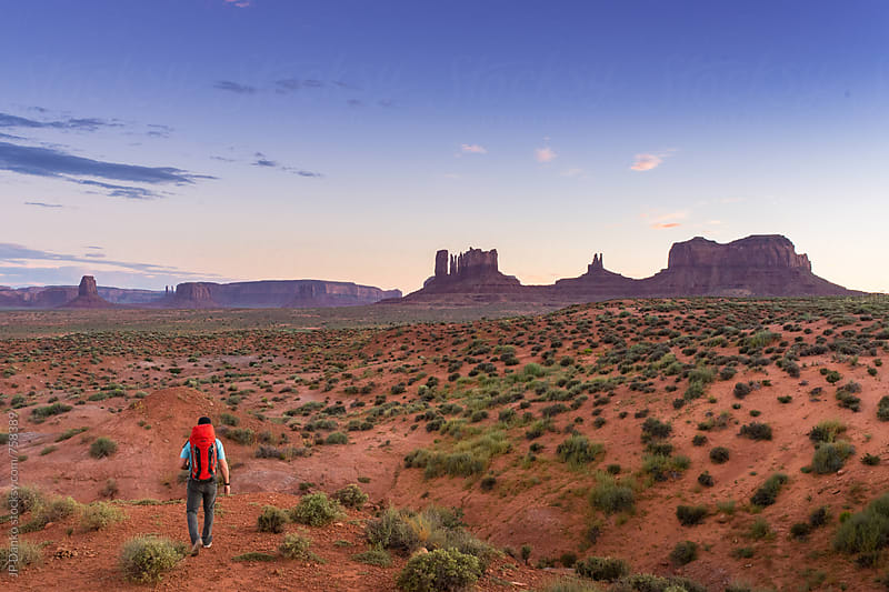 Man Backpacking In Monument Valley Utah At Dusk With Orange Backpack by JP Danko for Stocksy United