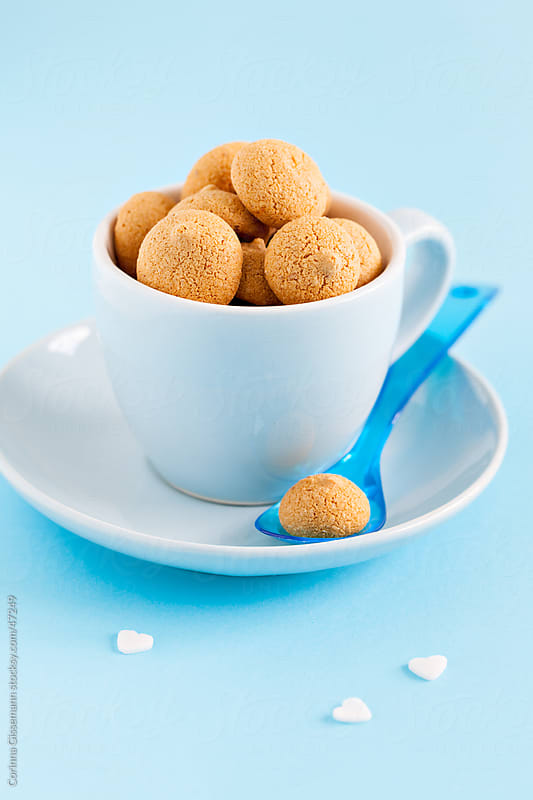 group of amaretti in a blue cup with spoon on blue background by Corinna Gissemann for Stocksy United