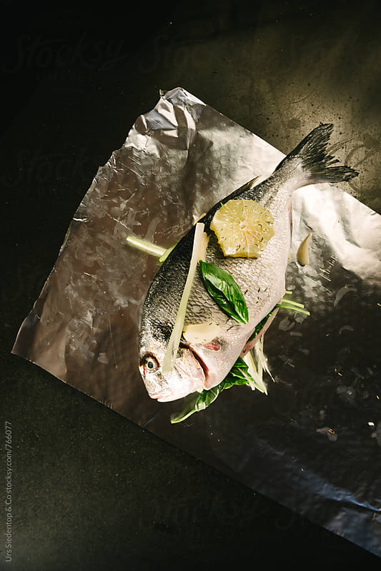 Fresh fish with lemon, garlic and herbs - gilthead seabream by Urs Siedentop & Co for Stocksy United