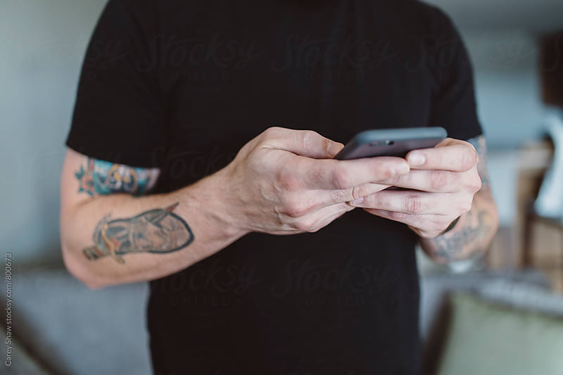 Detail of male with tattoos using his cell phone by Carey Shaw for Stocksy United