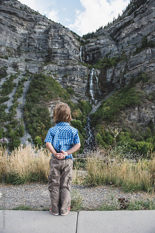 Young boy viewing waterfall  by Cameron Whitman for Stocksy United
