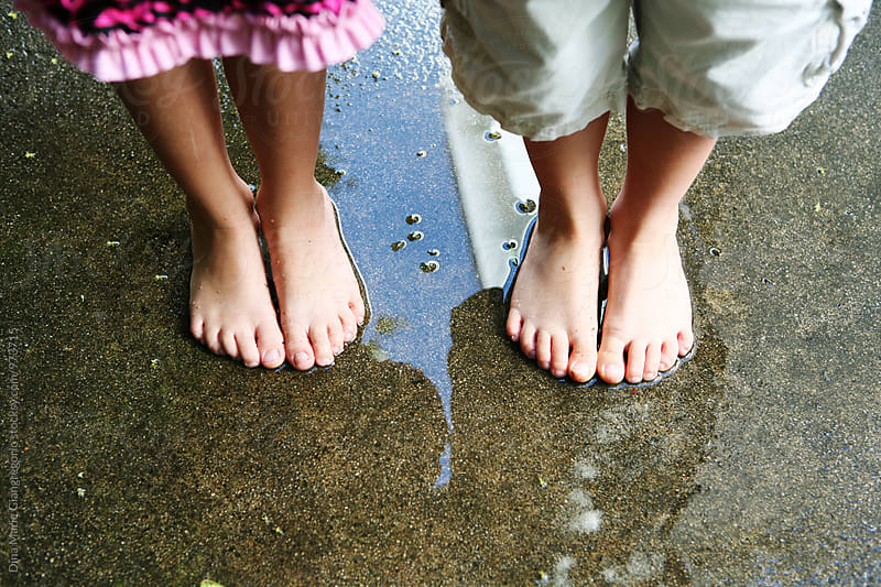 Boy and Girl's Legs and Feet Standing On Wet Ground by Dina Giangregorio for Stocksy United