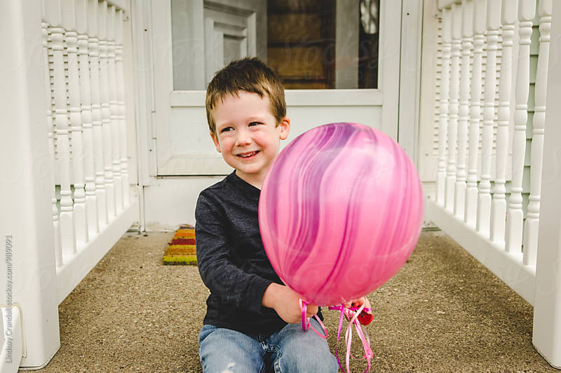 Happy boy holding a pink balloon by Lindsay Crandall for Stocksy United