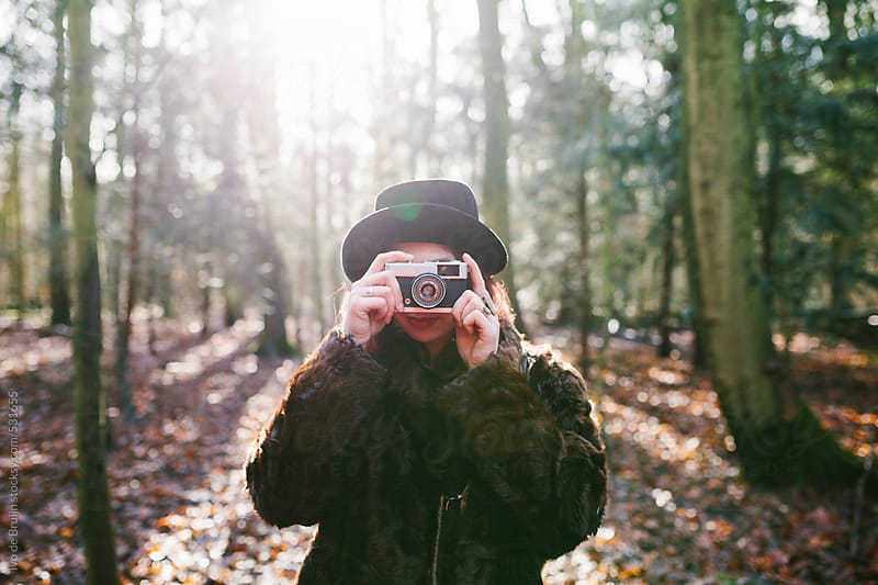 Young woman with a hat and a coat making photos with a camera in the forest by Ivo de Bruijn for Stocksy United