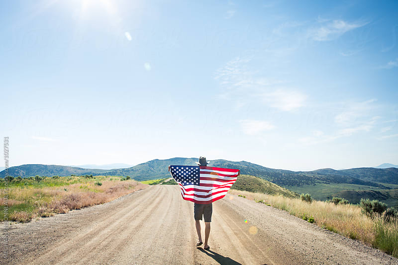 Man Holding American Flag on Dirt Road