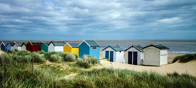 Brightly coloured beach huts on an overcast day in Southwold, Suffolk.  by kkgas for Stocksy United