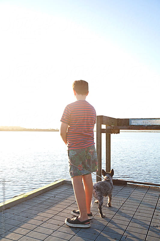 A young boy standing on a pier during sunset with his puppy by Natalie JEFFCOTT for Stocksy United