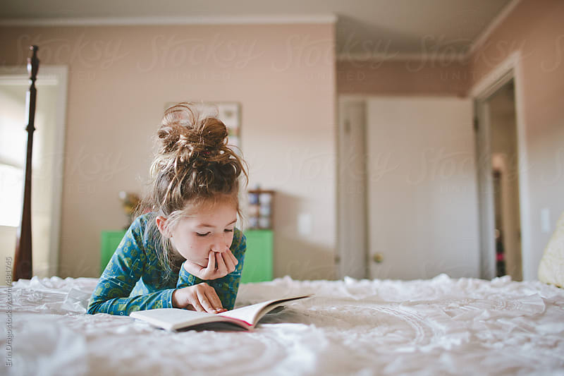 Girl reading on bed by Erin Drago for Stocksy United