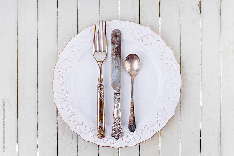 Antique Silver Fork, Spoon and Knife on White Plate by suzanne clements for Stocksy United