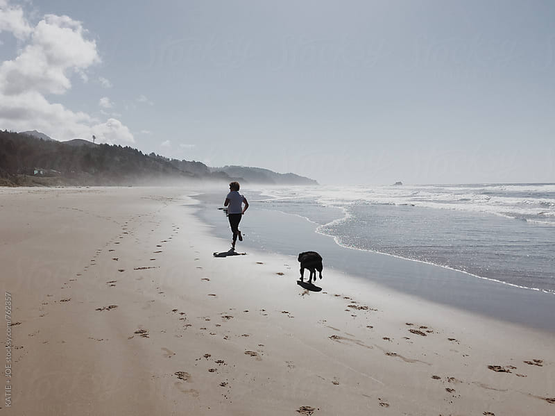 Man running on the beach with his dog by KATIE + JOE for Stocksy United