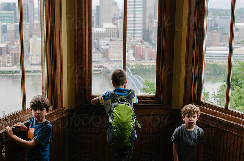 Three Brothers Look out a Window by Ali Deck for Stocksy United
