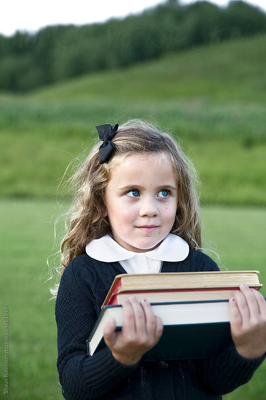 portrait of a girl holding some books in a field by Shaun Robinson for Stocksy United
