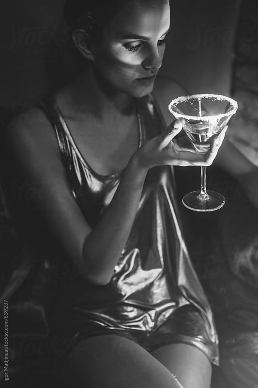 beautiful girl in modern dress sitting at the bar and having a drink by Igor Madjinca for Stocksy United
