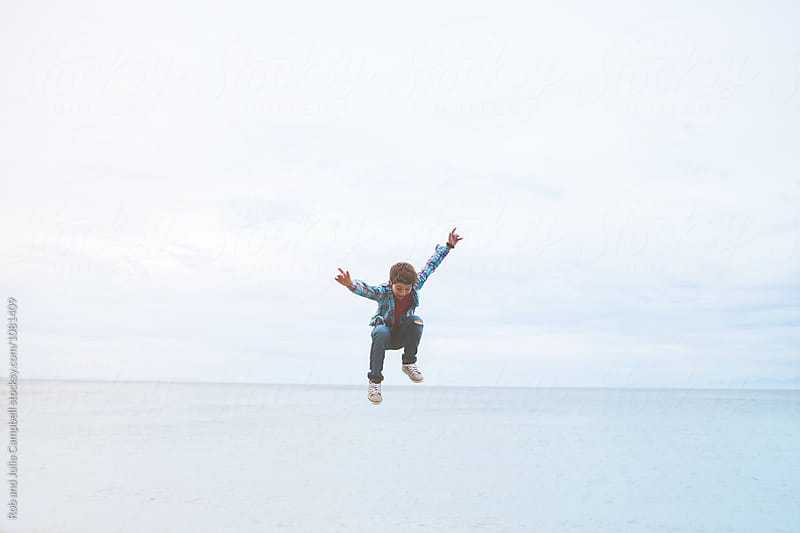 Young preteen caucasian boy outside in nature - jumping by Rob and Julia Campbell for Stocksy United