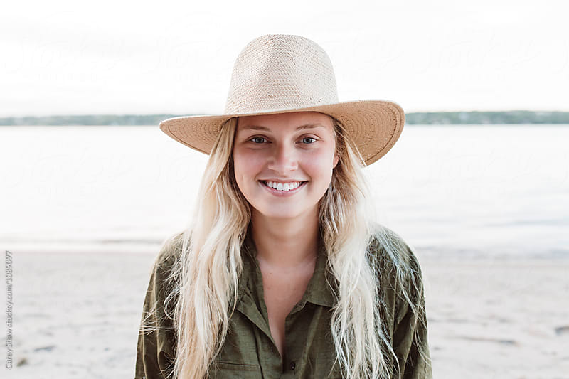Young woman at the beach wearing a straw hat by Carey Shaw for Stocksy United