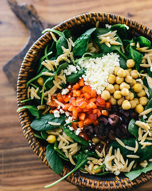 Close-up of nutritious greek orzo salad ingredients in basket by Trent Lanz for Stocksy United
