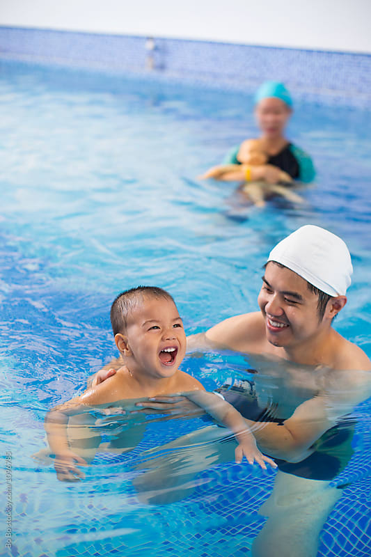 father and son in swimming pool by Bo Bo for Stocksy United