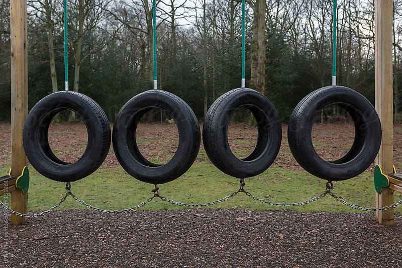 Group of tyres (tires) used as a swing in a children's outdoor play area by Paul Phillips for Stocksy United