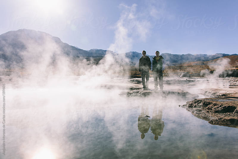 Two male friends next to a geyser - natural hot spring on adventure travel by Alejandro Moreno de Carlos for Stocksy United