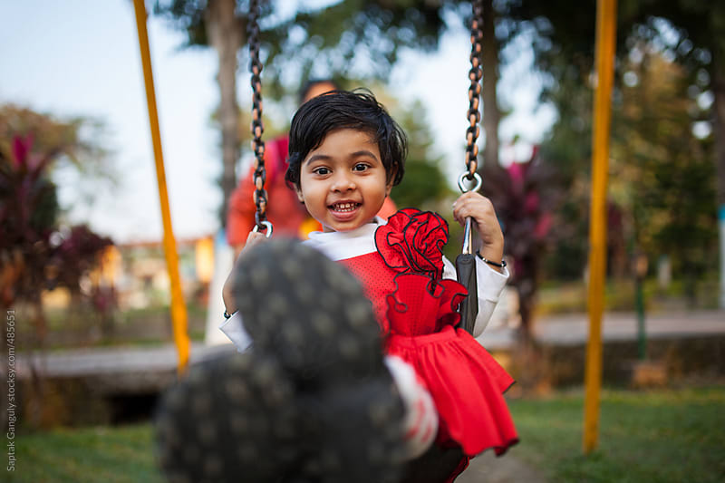 Cute toddler enjoying the swing in a park by Saptak Ganguly for Stocksy United