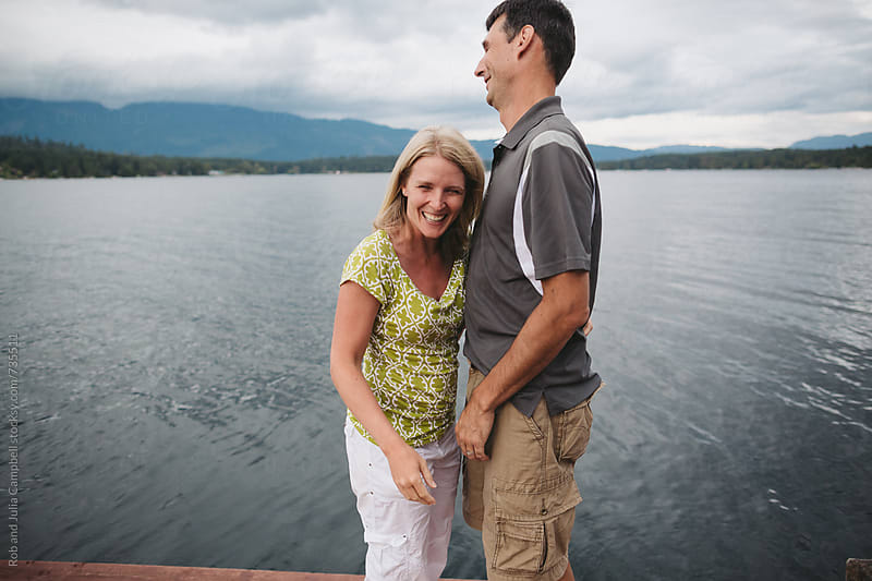 Happy couple in their 40's laughing awkwardly on the dock at the lake by Rob and Julia Campbell for Stocksy United