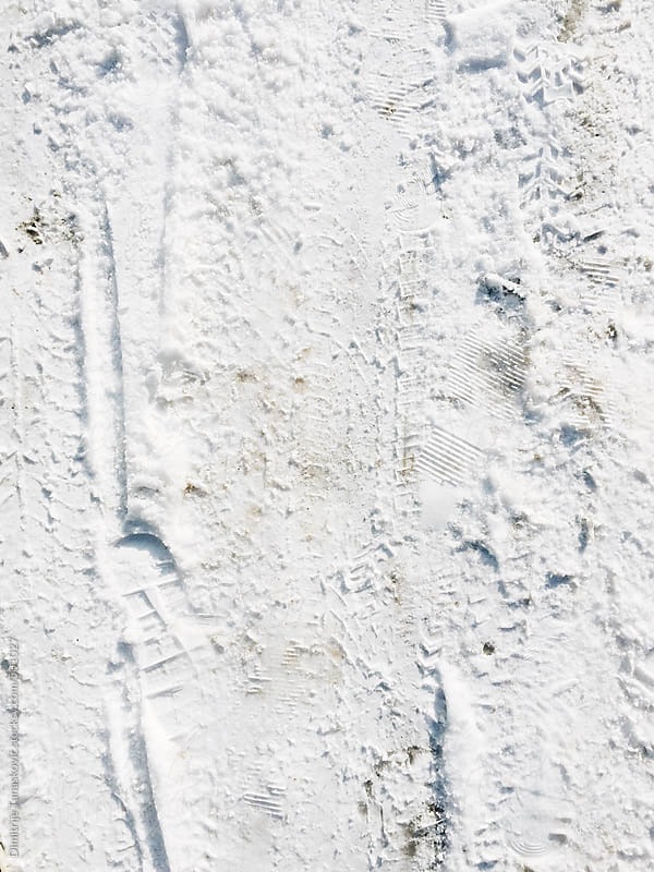 Footprints and car tracks on the city streets by Dimitrije Tanaskovic for Stocksy United