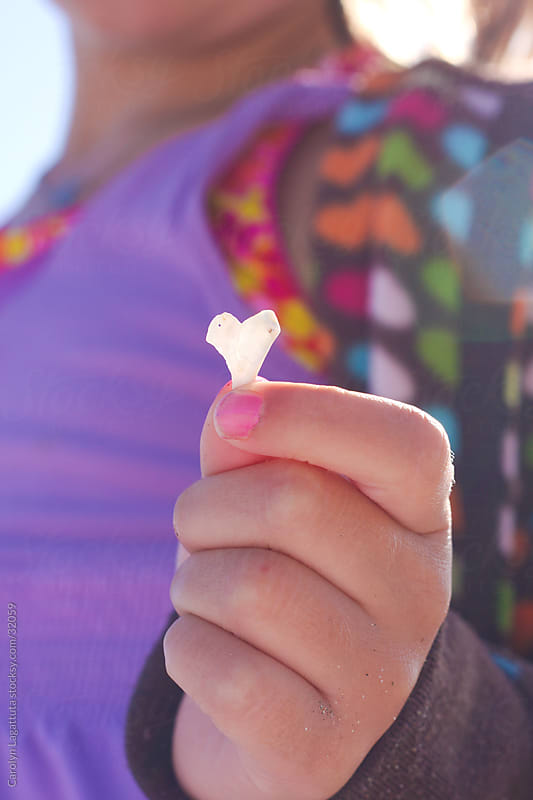 Young girl holding a heart shaped shell by Carolyn Lagattuta for Stocksy United